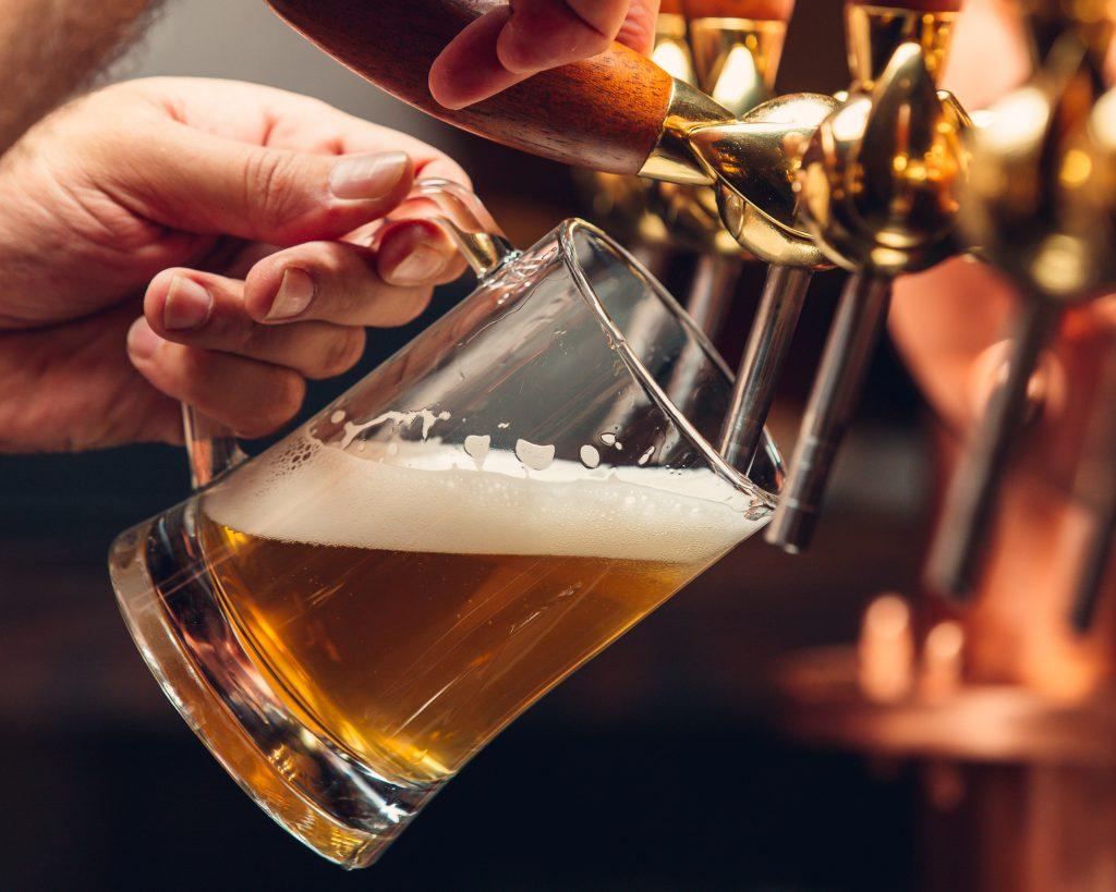 Camarero sirviendo jarra de cerveza.